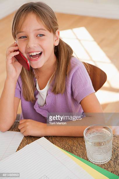 Young girl with mobile phone and homework at kitchen table