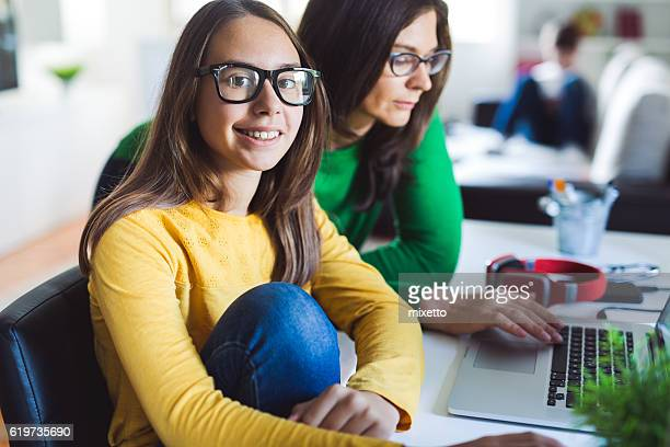 young girl with mother doing homework on the lap top - moving activity stock pictures, royalty-free photos & images