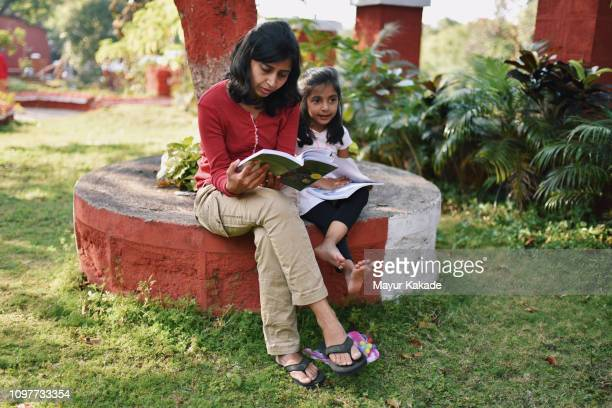 Young girl with mother reading book under the tree