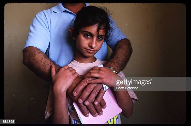 A young girl with ovarian cancer stands with her father May 1 1998 in Basra Iraq Depleted uranium was used extensively by UN troops during the Gulf...