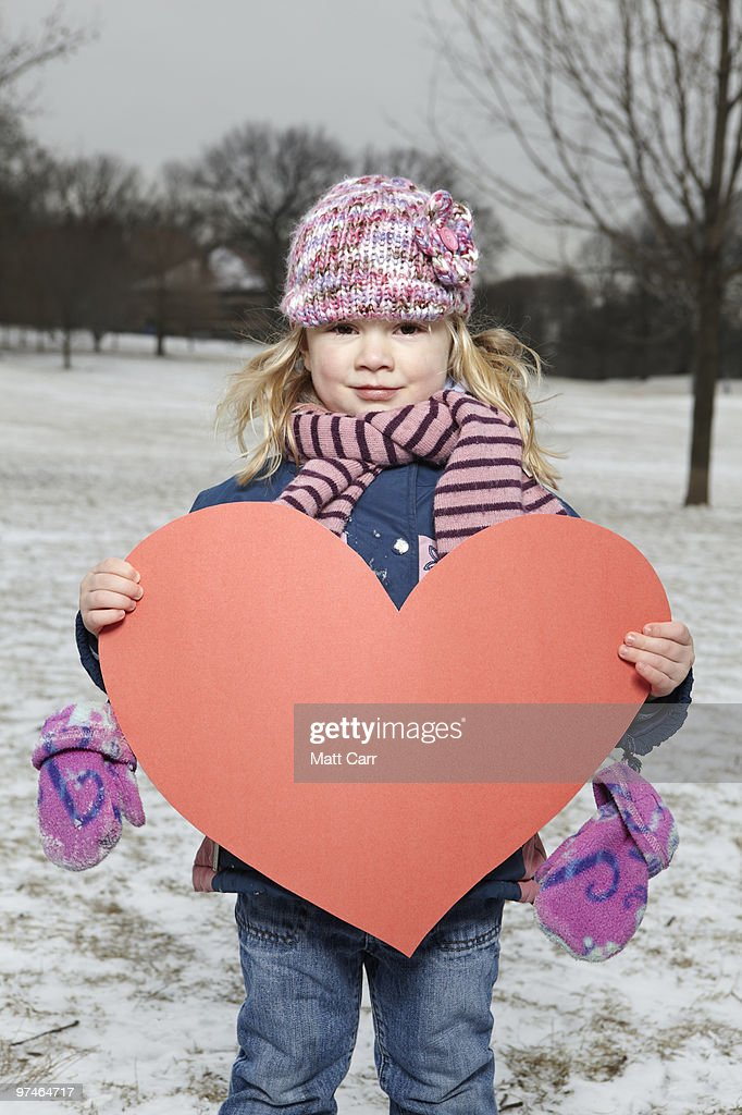 db733ac8d56 Young girl with Paper Heart in snowy park   Stock Photo