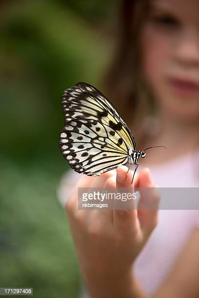 Young girl with paper kite butterfly on finger