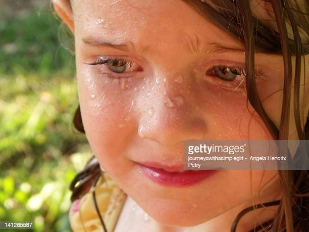 Young girl with pensive look on her wet face