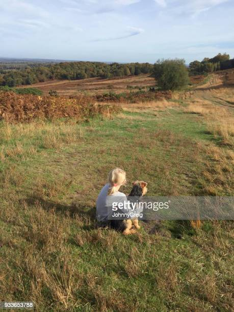 Young girl with pet dog sitting on grass together