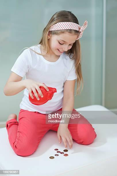 Young girl with piggy bank counting coins on bed