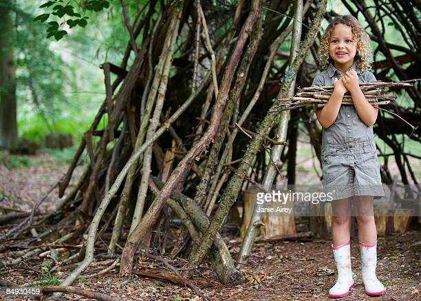 Young girl with pile of twigs in woods