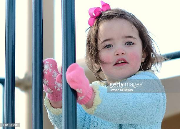 Young girl with pink mittens on playground