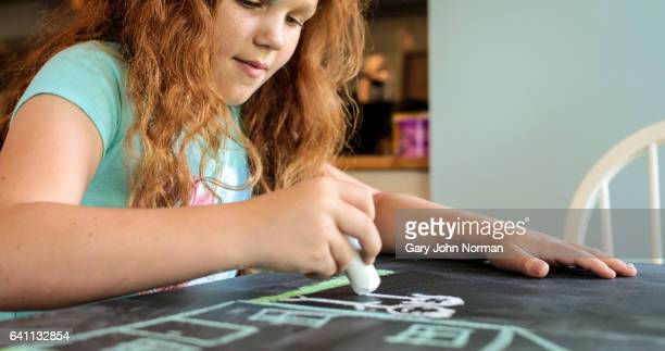 Young girl with red hair drawing a house on chalkboard.