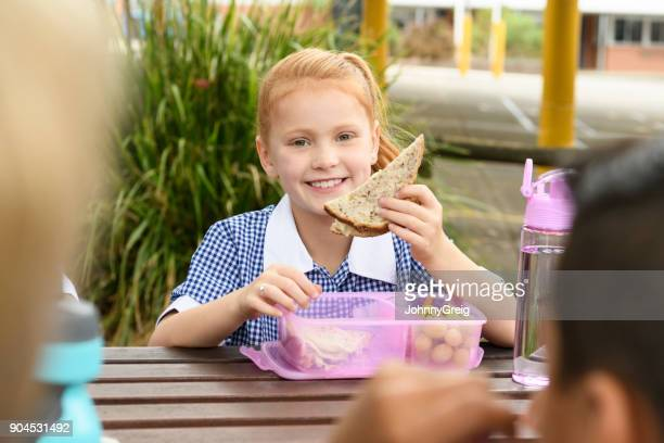Young girl with red hair eating sandwich on school lunch break