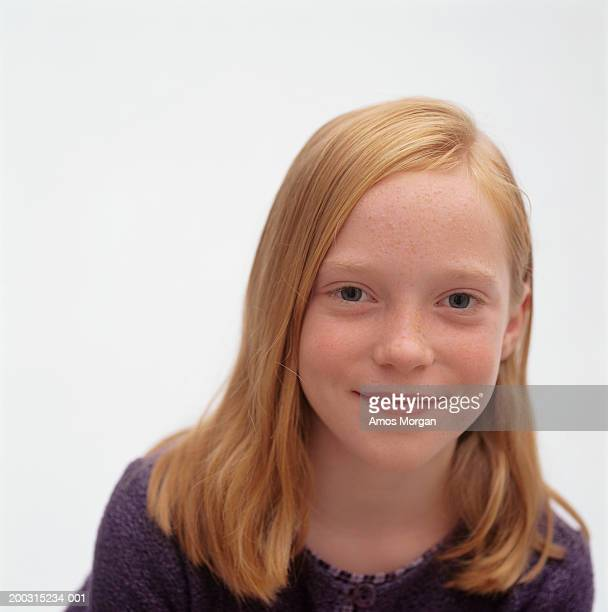 Young girl (10-11) with red hair posing in studio, close-up, portrait