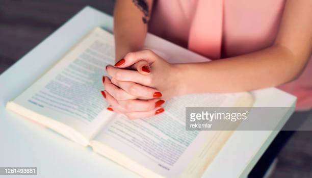young girl with red nail polish and tattoos praying over bible with her hands. religion. - judaism stock pictures, royalty-free photos & images
