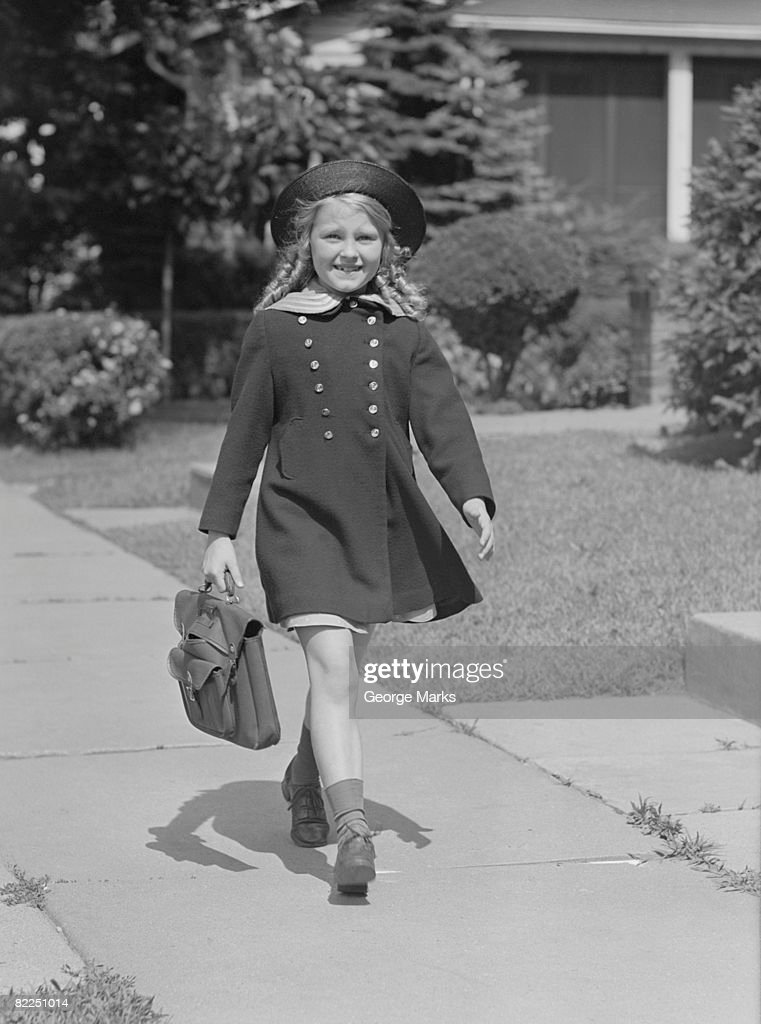 Young girl (8-9) with schoolbag on sidewalk, portrait : Stock Photo