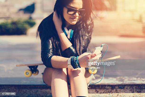 Young girl with skateboard texting on smartphone