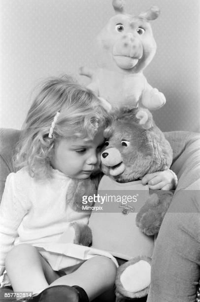 A young girl with soft toys sitting next to a Teddy Ruxpin toy 21st October 1986