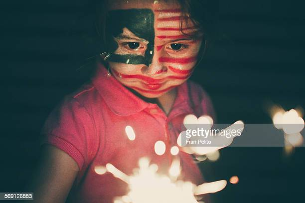 A young girl with sparkler and painted face.