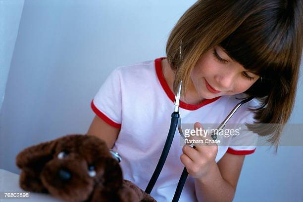 Young girl with stuffed dog pretending to be vet