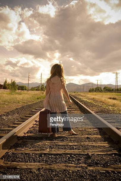 Young Girl with Suitcase Walking Along Train Tracks