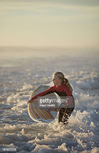 Young girl with surfboard in the ocean