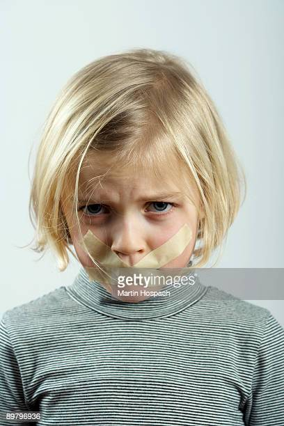 a young girl with tape over her mouth - forbidden stock photos and pictures