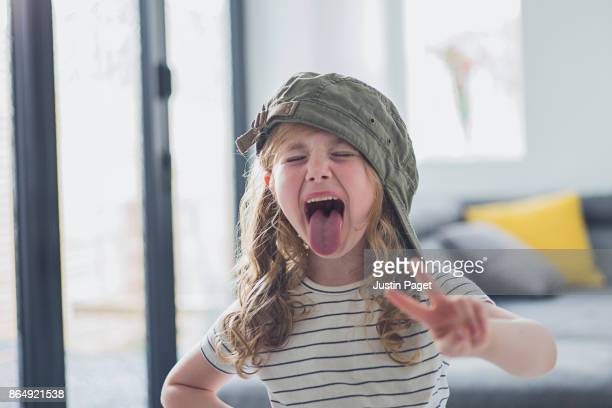 young girl with tongue out - little girl sticking out tongue stock photos and pictures