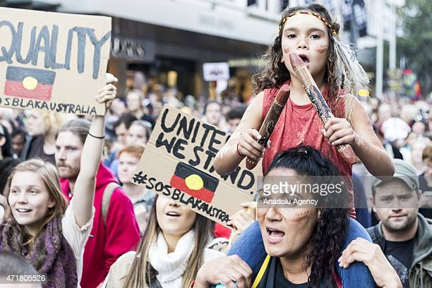 A young girl with traditional Aboriginal sticks seen on her mother shoulders during a rally protesting against the forced closure of Aboriginal...