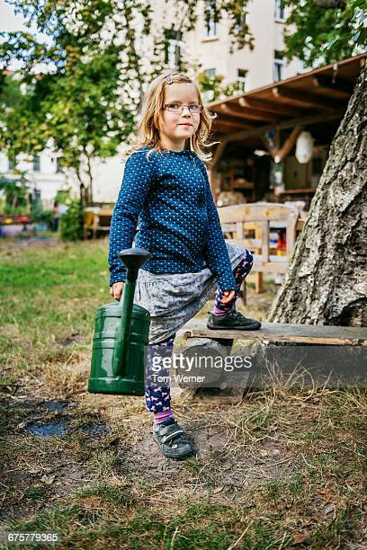 young girl with watering can - blonde glasses stock-fotos und bilder