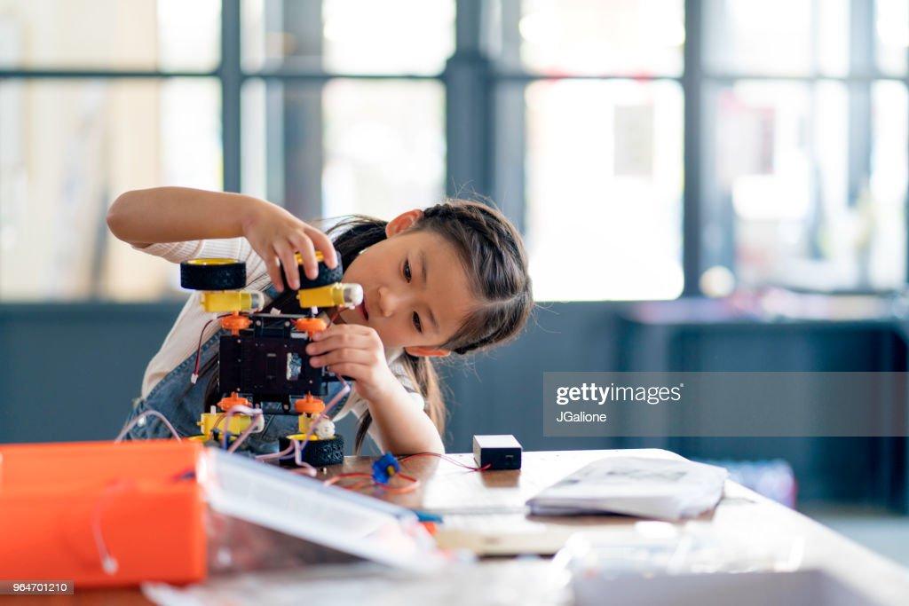 Jong meisje gewerkt aan het ontwerp van een robot : Stockfoto