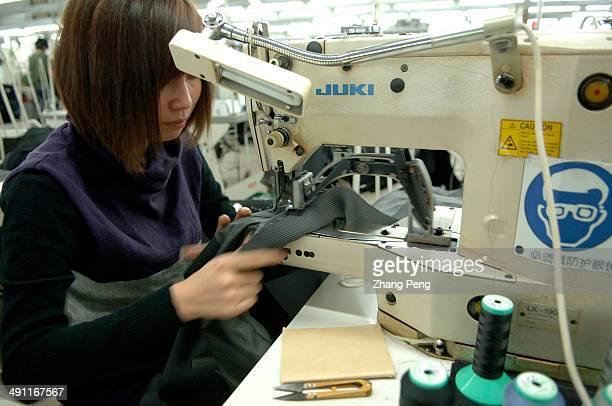 Young girl working on a sewing machine in a private garment factory in Jianyan, south of Jiangsu Province. Jiangsu, the same as Zhengjiang Province,...