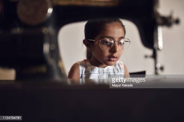young girl working on sewing machine wearing her grandmother's eyeglasses - rpg maker stock pictures, royalty-free photos & images