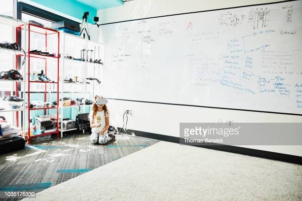 Young girl working with virtual reality headset while sitting on the floor in virtual reality lab
