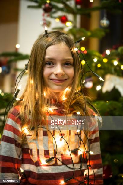 young girl wrapped in christmas lights in front of a christmas tree