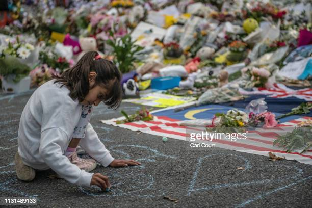 Young girl writes a message on the ground with chalk next to flowers and tributes near Al Noor mosque on March 19, 2019 in Christchurch, New Zealand....