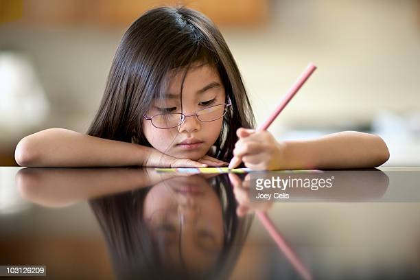 Young girl writing a letter on the kitchen table