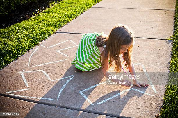 a young girl writing a recycling symbol on the sidewalk. - carbon footprint stock pictures, royalty-free photos & images