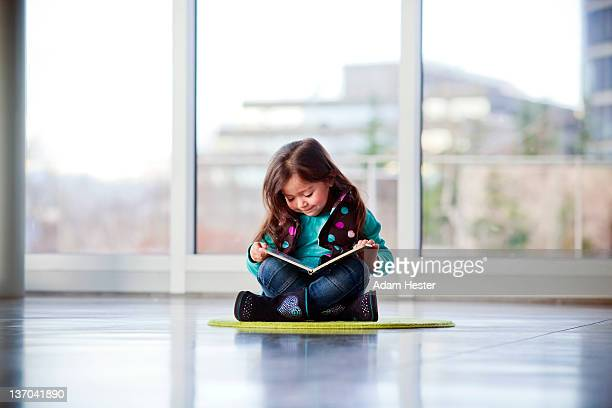 A young girl writing and playing inside a museum.