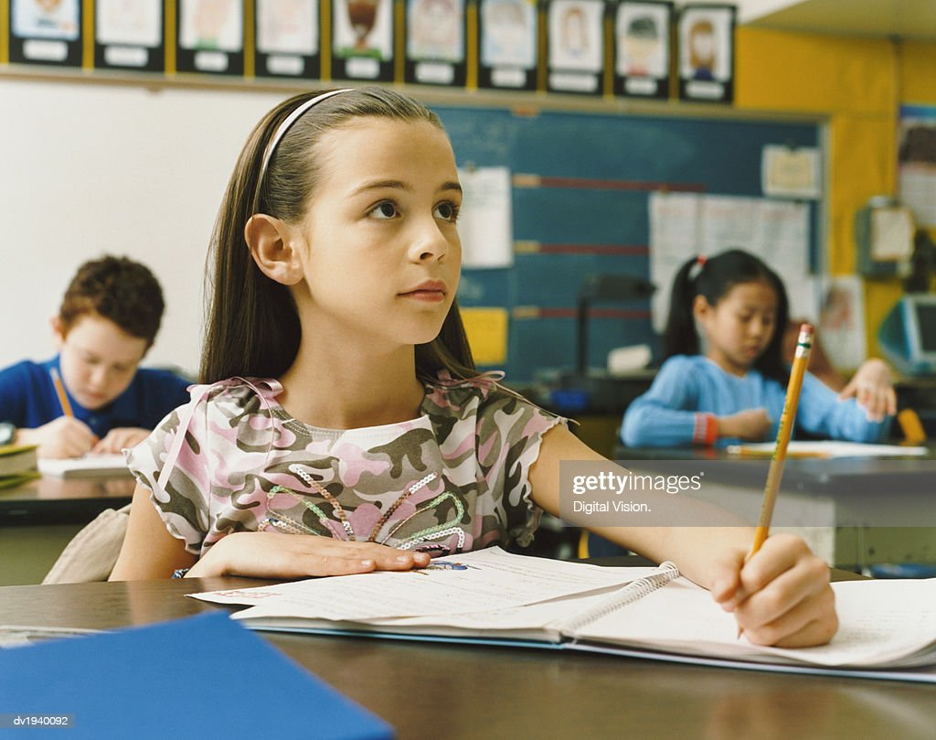 Young Girl Writing in Her Exercise Book in the Classroom : Stock Photo