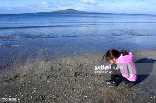 young girl writing in sand on a beach - rafael ben ari stockfoto's en -beelden