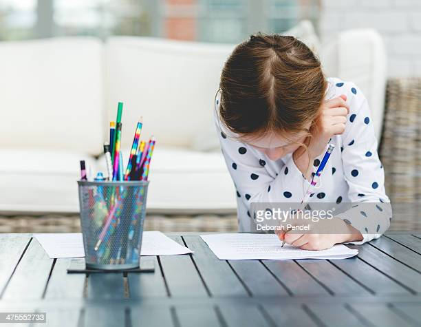 Young girl writing out her homework