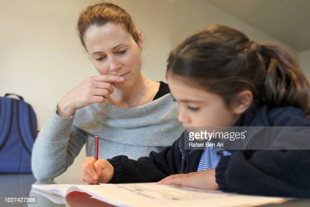 Young Girl Writting her  with the Help of her Mother
