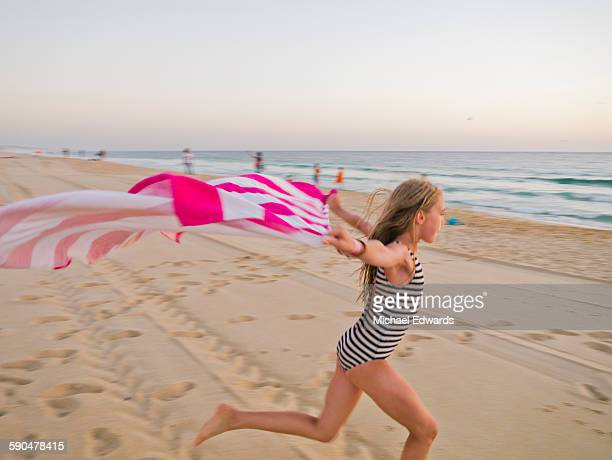 young girl wth striped towel on beach