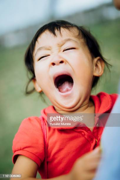 young girl yawning in the mother's arms - yawning mother child stock photos and pictures
