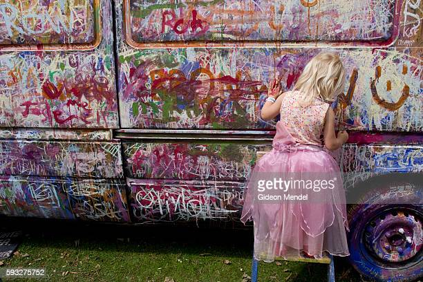 A young girld wearing a princess outfil draws on the side of Jan's infamous Van in the Kid's Garden area of Camp Bestival which takes place at...