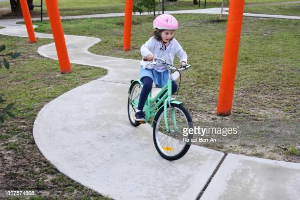 young girlriding on bicycle on a bike path - rafael ben ari fotografías e imágenes de stock