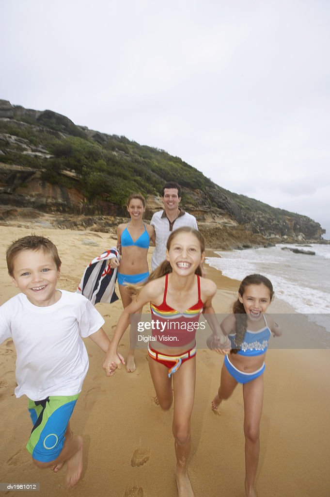 Young Girls and a Boy Run Along the Beach in Front of Their Parents : Stock Photo