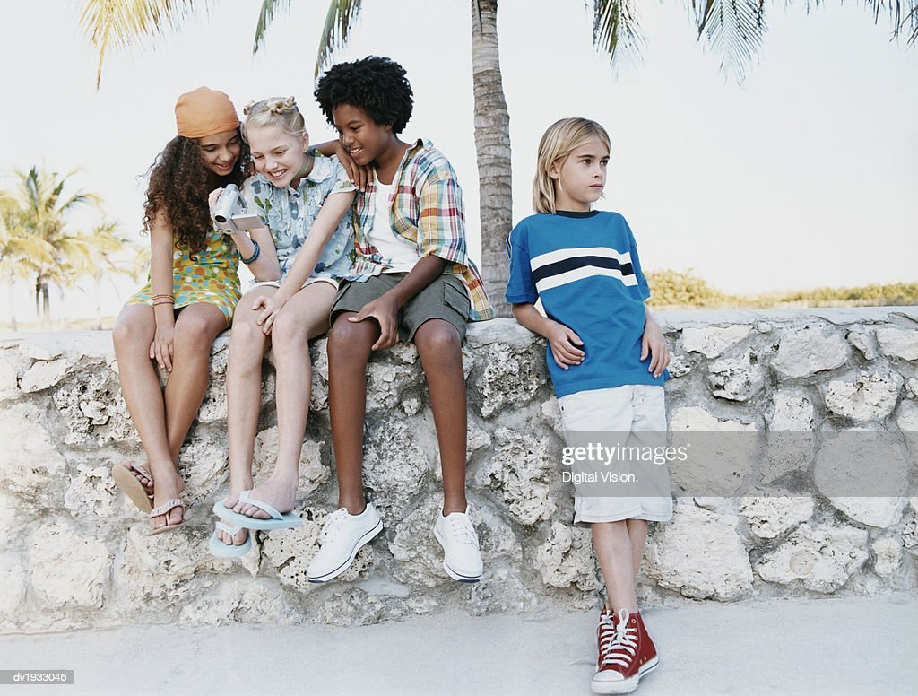 Young Girls and a Boy Sit on a Stone Wall Watching a Camcorder Video, Excluding a Boy Standing Next to Them : Stock Photo