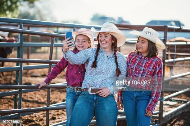 Jeunes filles et des adolescents au ranch en tenant selfies