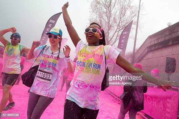 Young girls are seen covered in colourful chalk powder dance at the finish line after take part in Color Run 2016 in Paris France on April 17 2016...
