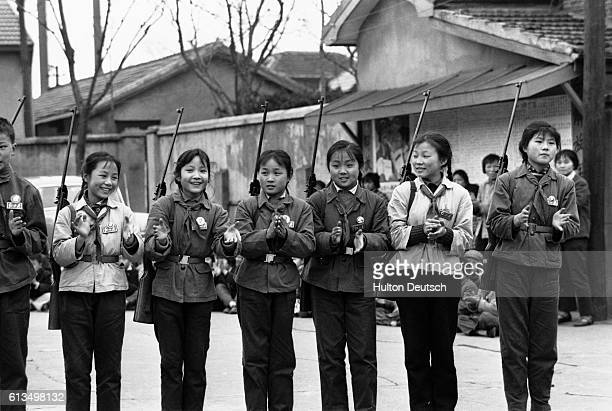 Young girls armed with air rifles wear Maoist Red Guard badges