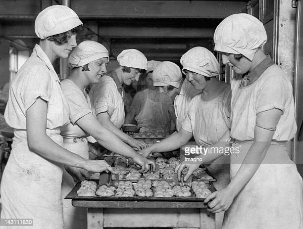 Young girls at a well known London Bakery busily engaged in stamping crosses on the Hot Cross Buns in readiness for the great demand on Good Friday...