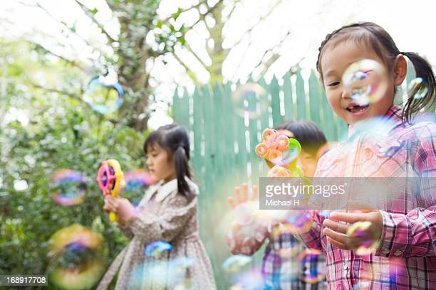 Young girls  blowing bubbles outdoor
